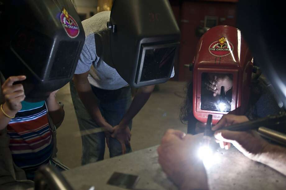 People watch a welding demonstration at a July open house at the Crucible in Oakland. Photo: Yue Wu, The Chronicle