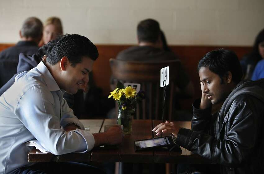 (Left to right) Roberto Santana, COO of Kloudless, looks at a tablet as Satish Polisetti, co-founder Picatcha scrolls through a display as they discuss work during the lunch hour at The Creamery.