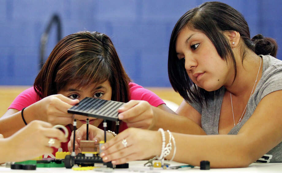 Naomi Zepeda, 14, (left) and her sister Alyssa Zepeda, 15, build a solar-powered model car with Lego parts during the GEAR UP (Gaining Early Awareness for Undergraduate Programs) event Saturday July 14, 2012 at the YMCA in the 1200 block of Iowa Street. GEAR UP is designed to help the class of 2017 prepare for success in higher education. The program which gives incoming 8th graders a way to study the STEM (Science, Technology, Engineering and Math) subjects is a partnership with the San Antonio Independent School Distric, the University of Texas at San Antonio, and the UTSA Interactive Technology Experience Center. While the students were building their cars, parents could attend college awareness workshops through the UTSA Mobile Go Center. Photo: Edward A. Ornelas, San Antonio Express-News / © 2012 San Antonio Express-News