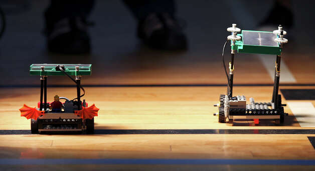 Lego solar-powered model cars race during the GEAR UP (Gaining Early Awareness for Undergraduate Programs) event Saturday July 14, 2012 at the YMCA in the 1200 block of Iowa Street. GEAR UP is designed to help the class of 2017 prepare for success in higher education. The program which gives incoming 8th graders a way to study the STEM (Science, Technology, Engineering and Math) subjects is a partnership with the San Antonio Independent School Distric, the University of Texas at San Antonio, and the UTSA Interactive Technology Experience Center. While the students were building their cars, parents could attend college awareness workshops through the UTSA Mobile Go Center. Photo: Edward A. Ornelas, San Antonio Express-News / © 2012 San Antonio Express-News