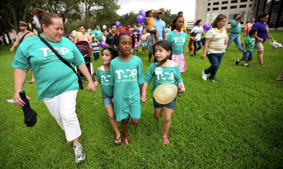 Sylvia Lugo, left, walks with her granddaughter Jasmyn Rodriguez, her friend Madison Hermann, center, and other granddaughter Jizel Rodriguez to a Post Oak Blvd. protest for pay wages for janitors during a City Wide Children's Day of Action. Photo: Nick De La Torre, Houston Chronicle / © 2012  Houston Chronicle