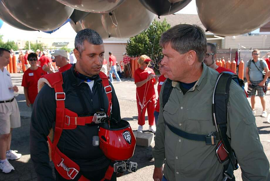 Gas station owner Kent Couch, right, confers with Iraqi adventurer Fareed Lafta  before taking off from Bend, Ore., in tandem lawn chairs suspended from helium-filled party balloons, Saturday, July 14, 2012 in Bend, Ore.. The two men hoped to fly across Oregon, Idaho and into Montana. (AP Photo/Jeff Barnard) Photo: Jeff Barnard, Associated Press