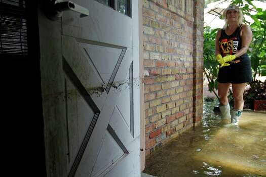 Jeannette Harris is planning a cleanup party after flood­waters rose Friday to almost  3 feet in the garage and 18 inches in her Wildwood sub­division home in the Cypress area. Photo: Melissa Phillip / © 2012 Houston Chronicle