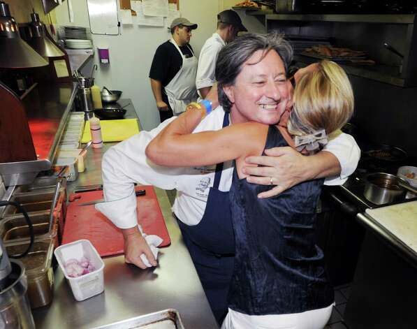 Chef Jean-Louis Gerin, left, of Restaurant Jean-Louis, hugs Renée Ketcham, president of Alliance Française of Greenwich, in the kitchen of his Greenwich restaurant during Bastille Day, Saturday night, July 14, 2012. Restaurant Jean-Louis and the Alliance Française of Greenwich hosted a Bastille Day street party on Lewis Street. Photo: Bob Luckey / Greenwich Time