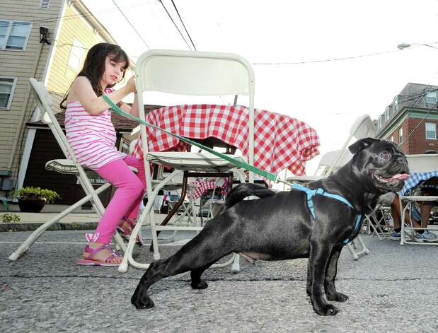 Alexis Newman, 8, of Greenwich, and her pug puppy named Magnus during the Bastille Day street party on Lewis Street in Greenwich, Saturday night, July 14, 2012. The event was hosted by Restaurant Jean-Louis and the Alliance Française of Greenwich. Photo: Bob Luckey / Greenwich Time
