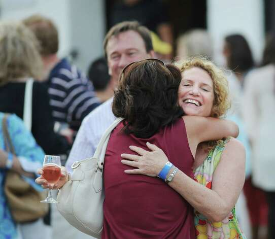 Beth Wright of Greenwich hugs a friend during the Bastille Day street party on Lewis Street in Greenwich, Saturday night, July 14, 2012. The event was hosted by Restaurant Jean-Louis and the Alliance Française of Greenwich. Photo: Bob Luckey / Greenwich Time