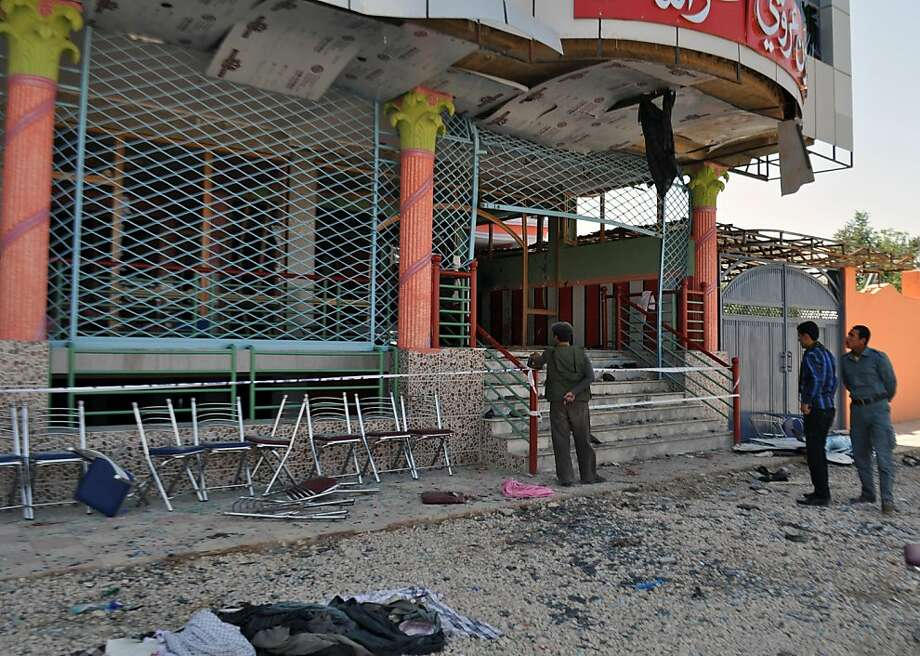 Onlookers and police are seen at the entrance of a damaged wedding hall, where a suicide bomber detonated himself killing a prominent Afghan lawmaker and 16 others, in Aybak city, capital of Samangan province, on July 14 , 2012.  A suicide bomber killed a prominent Afghan lawmaker and 16 other people at his daughter's wedding party in the north of the country on July 14, officials said. The attacker embraced MP Ahmad Khan, a former militia commander, in front of wedding guests before detonating the explosives strapped around his waist, a security forces spokesman said. AFP PHOTO/STRSTR/AFP/GettyImages Photo: Str, AFP/Getty Images