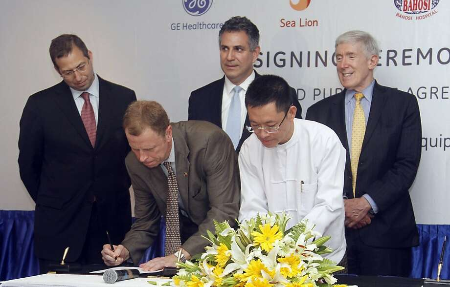 President and CEO of General Electric ASEAN, Stuart Dean, second from left, signs documents during the signing ceremony between Sea Lion Co. Ltd., General Electric Healthcare and Bahosi and Pun Hlaing Hospitals in Yangon, Myanmar, Saturday, July. 14, 2012. General Electric became the first American firm to sign a business deal in Myanmar after Washington eased key investment sanctions on the former pariah state. Witness at the signing are from left., U.S. ambassador to Myanmar Derek Mitchell, Stuart Dean, U.S. Under Secretary of Commerce for International Trade, Francisco Sanchez, and U.S. Under Secretary of State for Economic Growth, Energy and the Environment, Robert Hormats, right. At second right is an unidentified local assistant. (AP Photo/Khin Maung Win) Photo: Khin Maung Win, Associated Press