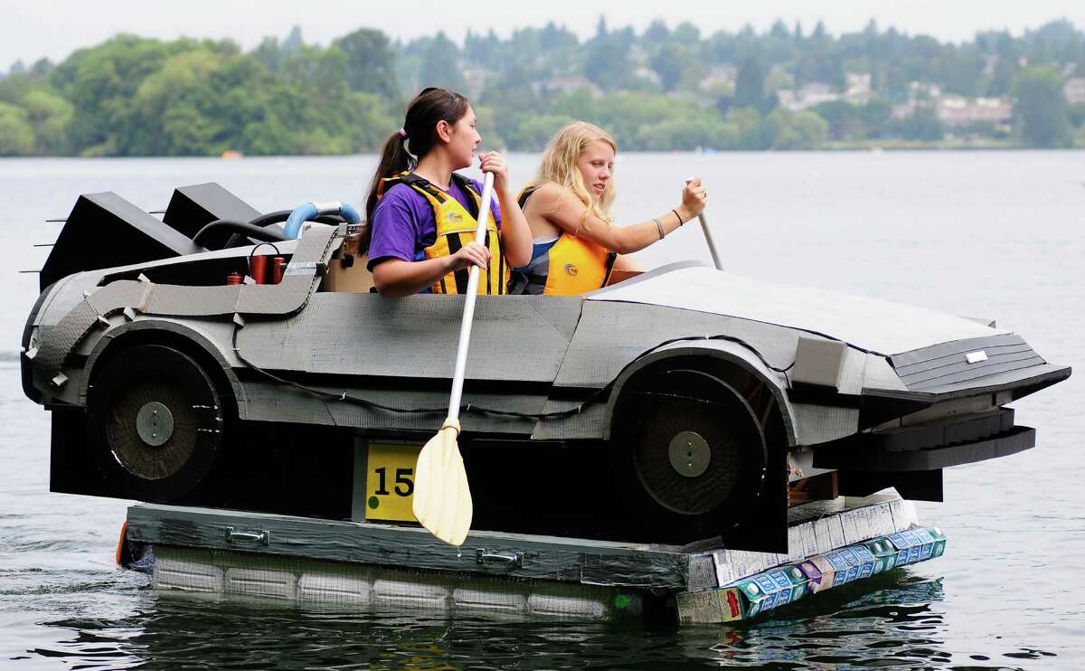 Two girls paddle a DeLorean during the 42nd annual Seafair Milk Carton Derby at Green Lake in Seattle on Saturday, July 14, 2012. Many creatively designed boats competed in races and a