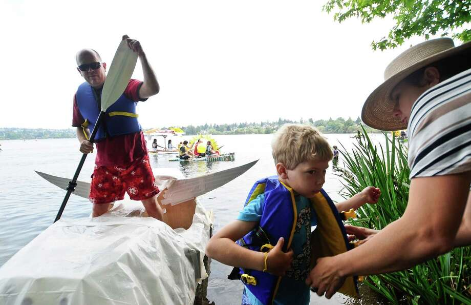 Dominik Parker, 7, is given a life vest by his mother, Jana Brabcova, as he gets on a boat with his father, John Parker. Photo: LINDSEY WASSON / SEATTLEPI.COM