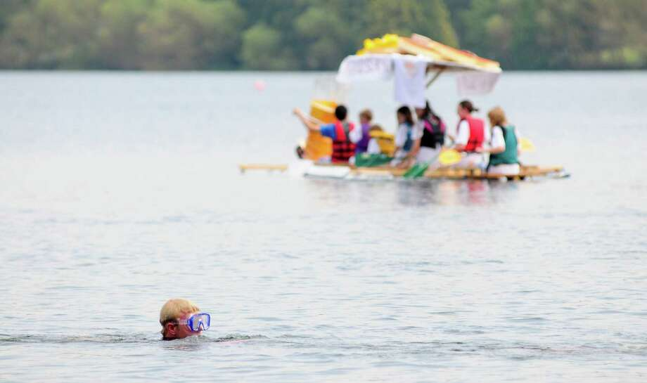 A lone swimmer follows boats as he films them with an underwater camera. Photo: LINDSEY WASSON / SEATTLEPI.COM