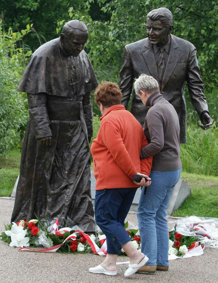 People look at a new statue of former President Ronald Reagan and Pope John Paul II that was unveiled in Gdansk, Poland, on Saturday, July 14, 2012. The statue honors the two men whom many Poles credit with helping to topple communism. (AP Photo/Czarek Sokolowski) Photo: Czarek Sokolowski