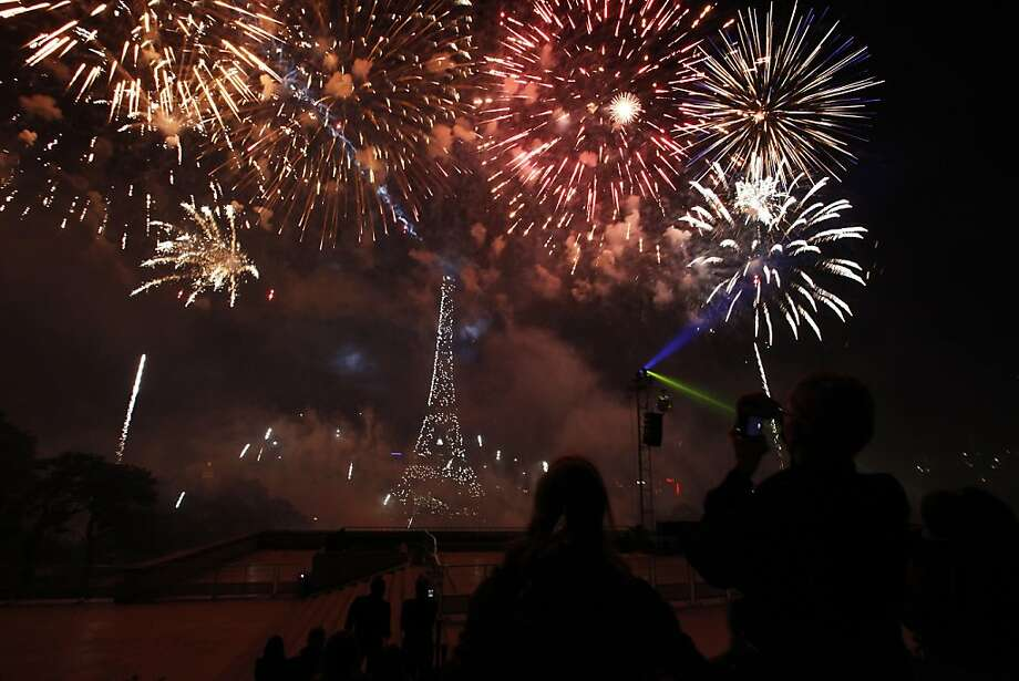 People watch as fireworks illuminate the night sky near the Eiffel Tower during the annual Bastille Day celebrations on July 14, 2012 in Paris.  AFP PHOTO / GUILLAUME BAPTISTEGUILLAUME BAPTISTE/AFP/GettyImages Photo: Guillaume Baptiste, AFP/Getty Images