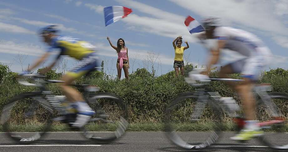 Two women wave the French national flag on Bastille Day as riders pass during the 13th stage of the Tour de France cycling race over 217 kilometers (134.8 miles) with start in Saint-Paul-Trois-Chateaux and finish in Le Cap D'Agde, France, Saturday July 14, 2012. (AP PhotoLaurent Cipriani) Photo: Laurent Cipriani, Associated Press