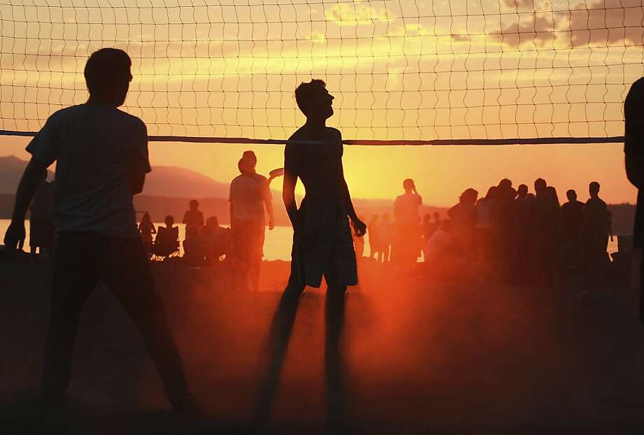 In this July 12, 2012 photo, people play volleyball on Golden Gardens beach at sunset in Seattle.  (AP Photo/The Seattle Times, John Lock)  MAGS OUT; NO SALES; SEATTLEPI.COM OUT; MANDATORY CREDIT Photo: John Lok, Associated Press