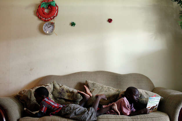 Congolese refugees and brothers John Kulimushi, 4, left, and Shokano Kulimushi, 6, look at books on the couch in the apartment they share with their mother and 6 other siblings at Auburn Creek Apartments in San Antonio on Saturday, July 14, 2012. The family is facing eviction this week. Photo: Lisa Krantz, San Antonio Express-News / San Antonio Express-News