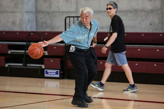 Volunteer Gordon Chin from the Chinatown Community Development center dribbles a ball on the newly constructed gym at the Chinese Recreation Center in San Francisco, Calif., on Thursday,  July 12, 2012.  Gordon Chin was on the recreation and park commission when the project started 10 years ago.  Behind him is an electric retractable bleacher seats. Photo: Liz Hafalia, The Chronicle