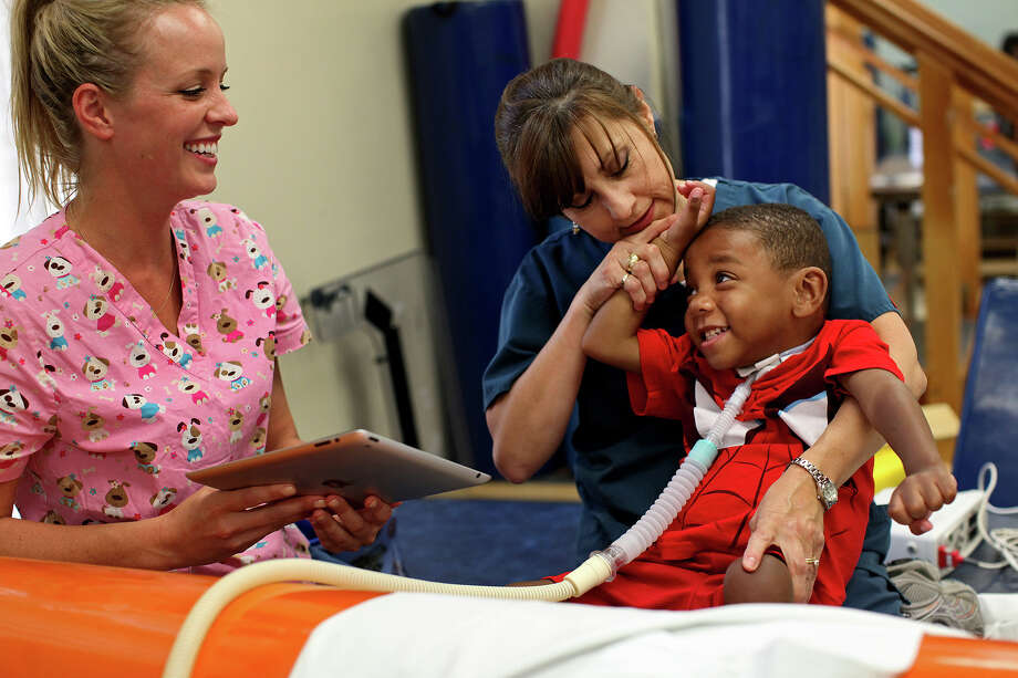 Physical therapist Selina Morgan, right, and occupational therapist Revi Hawley, left, work to get Braylon Nelson, 2, to move his hands and arms as his mother, Candice Matthews, left, encourages him during a session at CHRISTUS Santa Rosa Children's Hospital in San Antonio on Thursday, July 5, 2012. Photo: Lisa Krantz, San Antonio Express-News / San Antonio Express-News