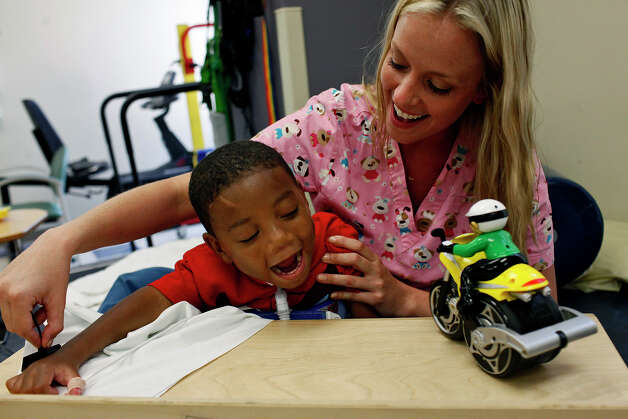 Occupational therapist Revi Hawley works with Braylon Nelson, 2, getting him to put pressure with his hand on a sensor to make the toy, at right, move, at CHRISTUS Santa Rosa Children's Hospital in San Antonio on Thursday, July 5, 2012. Photo: Lisa Krantz, San Antonio Express-News / San Antonio Express-News