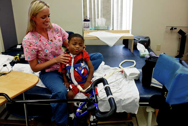 Braylon Nelson, 2, with occupational therapist Revi Hawley, shows his uncertainty about getting on a modified bicycle during therapy at CHRISTUS Santa Rosa Children's Hospital in San Antonio on Thursday, July 5, 2012. Photo: Lisa Krantz, San Antonio Express-News / San Antonio Express-News