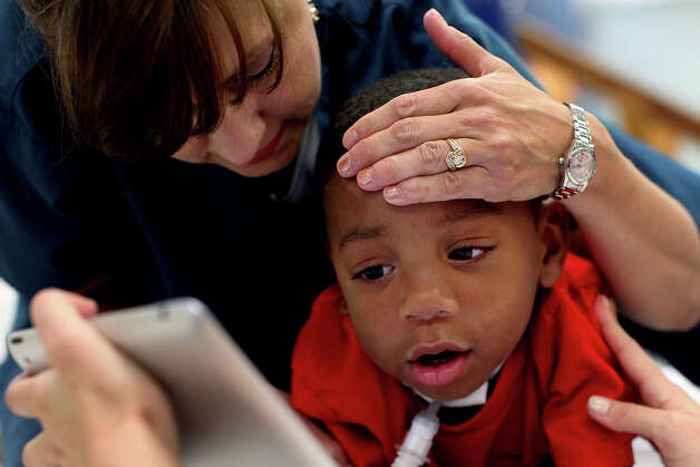 Physical therapist Selina Morgan works with Braylon Nelson, 2, during a session at CHRISTUS Santa Rosa Children's Hospital in San Antonio on Thursday, July 5, 2012. Photo: Lisa Krantz, San Antonio Express-News / San Antonio Express-News
