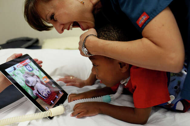Physical therapist Selina Morgan works to get Braylon Nelson, 2, to use his hands and arms during a session at CHRISTUS Santa Rosa Children's Hospital in San Antonio on Thursday, July 5, 2012. Photo: Lisa Krantz, San Antonio Express-News / San Antonio Express-News