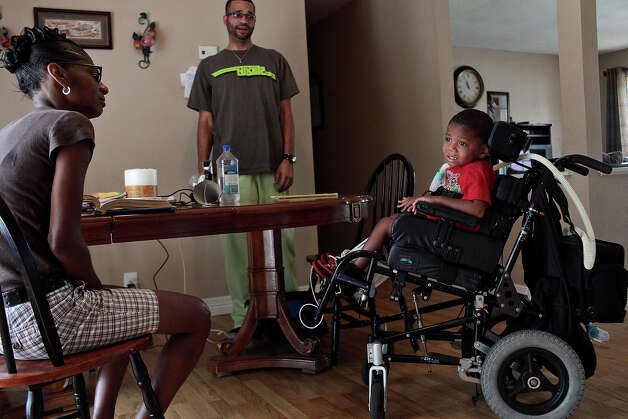 Braylon Nelson, 2, who was paralyzed in a road rage accident, waits with his grandma, Rhodena Matthews, left, for Charles Pillot, a licensed medical massage practitioner, center, to give him a haircut at his home in San Antonio on Friday, June 29, 2012. Photo: Lisa Krantz, San Antonio Express-News / San Antonio Express-News