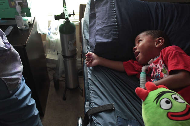 Braylon Nelson, 2, who was paralyzed in a road rage accident, waits to get suctioned by RN Noni Battle at his home in San Antonio on Friday, June 29, 2012. Nelson receives 24-hour nursing care. Photo: Lisa Krantz, San Antonio Express-News / San Antonio Express-News