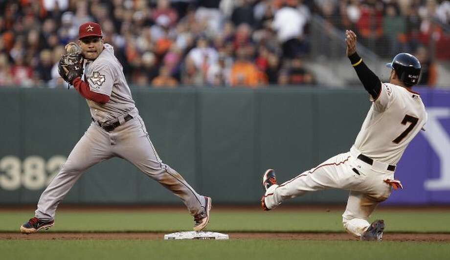 Houston Astros second baseman Jose Altuve, left, prepares to complete a double play over San Francisco Giants' Gregor Blanco (7) in the sixth inning. (Ben Margot / Associated Press)