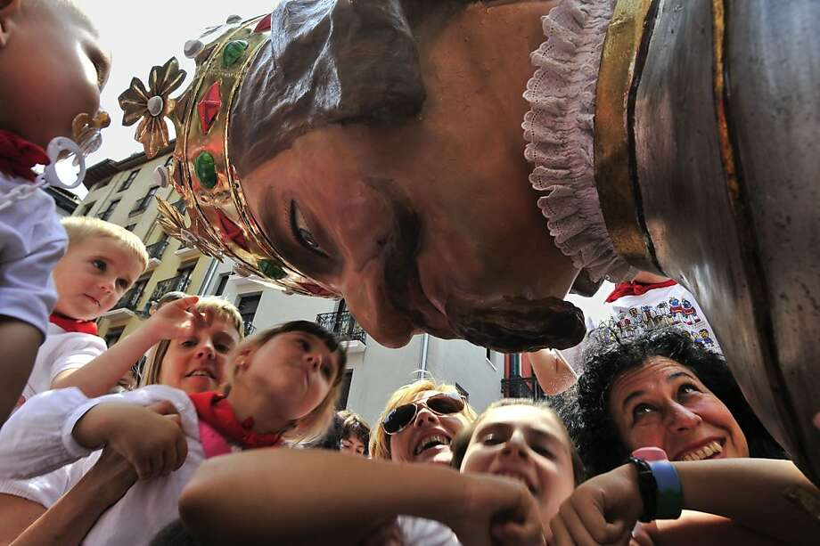 """''Pamplonicas'' greet a costumed figure, at the San Fermin fiestas, in Pamplona, northern Spain, Saturday, July 14, 2012. The festival of San Fermin will end at midnight Saturday, with the singing of the ''Pobre de Mi"""". (AP Photo/Alvaro Barrientos) Photo: Alvaro Barrientos, Associated Press"""