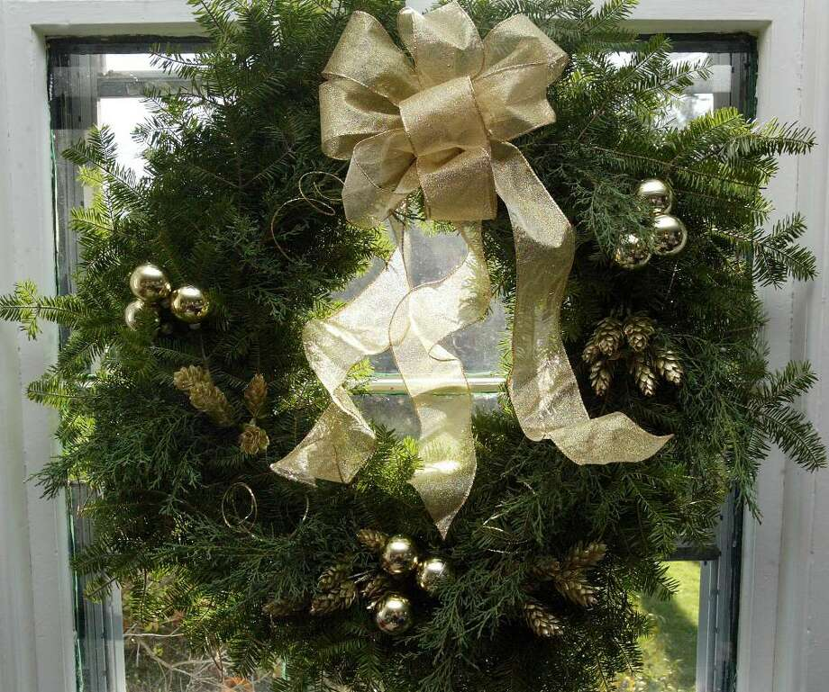 A finished wreath decorates a window atthe Starkweather House in Nichols while members of the Nichols Garden Club prepare wreaths and other items for the 25 Holiday Boutique, Friday, Dec 4, 12-5 and Saturday, Dec. 5, 10-2. Sunday, Nov 29, 2009. Photo: Phil Noel / Connecticut Post