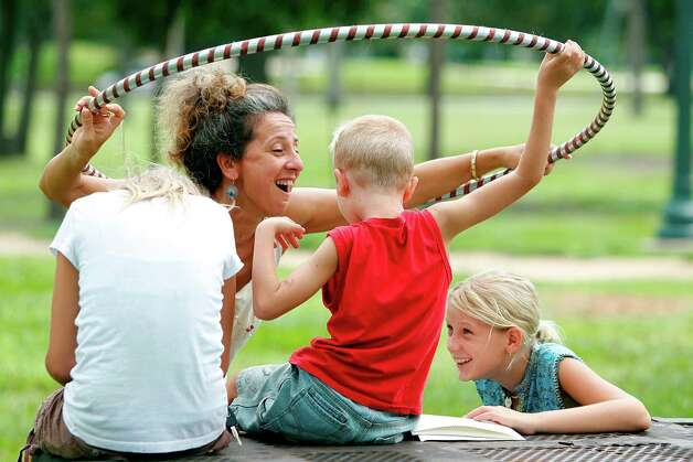 Anna Calvara plays with her children Ravi Whitright, 7, and Gaiamrita Whitright, 10, during the 'Sunday Hooping at the Park' meet-up organized by Houston Hooper Stahs at Hermann Park before the rain on Sunday, July 15, 2012. Photo: Mayra Beltran, Houston Chronicle / © 2012 Houston Chronicle