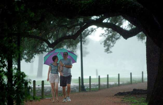 Downpours Sunday soak Nellie Nikova and Boris Popov in Hermann Park. Photo: Mayra Beltran, Houston Chronicle / © 2012 Houston Chronicle