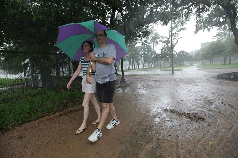 Nellie Nikova and Boris Popov are caught in the rain and slowly make their way to their car Sunday, July 15, 2012, at Hermann Park in Houston. Rain will continue through the start of the week. Photo: Mayra Beltran, Houston Chronicle / © 2012 Houston Chronicle