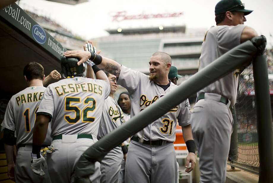 Oakland Athletics' Yoenis Cespedes (52) celebrates with teammates, including Jonny Gomes, in the dugout after his second-inning home run against the Minnesota Twins during a baseball game, Sunday, July 15, 2012, in Minneapolis. (AP Photo/The Star Tribune, Jeff Wheeler)  MANDATORY CREDIT; ST. PAUL PIONEER PRESS OUT; MAGS OUT; TWIN CITIES TV OUT Photo: Jeff Wheeler, Associated Press