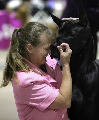Laura Coomes embraces her black Great Dane, Scout, after winning Best in Show during the River City Cluster of Dog Shows for Bexar County Kennel Club on Sunday, July 15, 2012 at Freeman Coliseum. Scout won three best in shows in a row this weekend. Photo: Julysa Sosa, San Antonio Express-News / SAN ANTONIO EXPRESS-NEWS