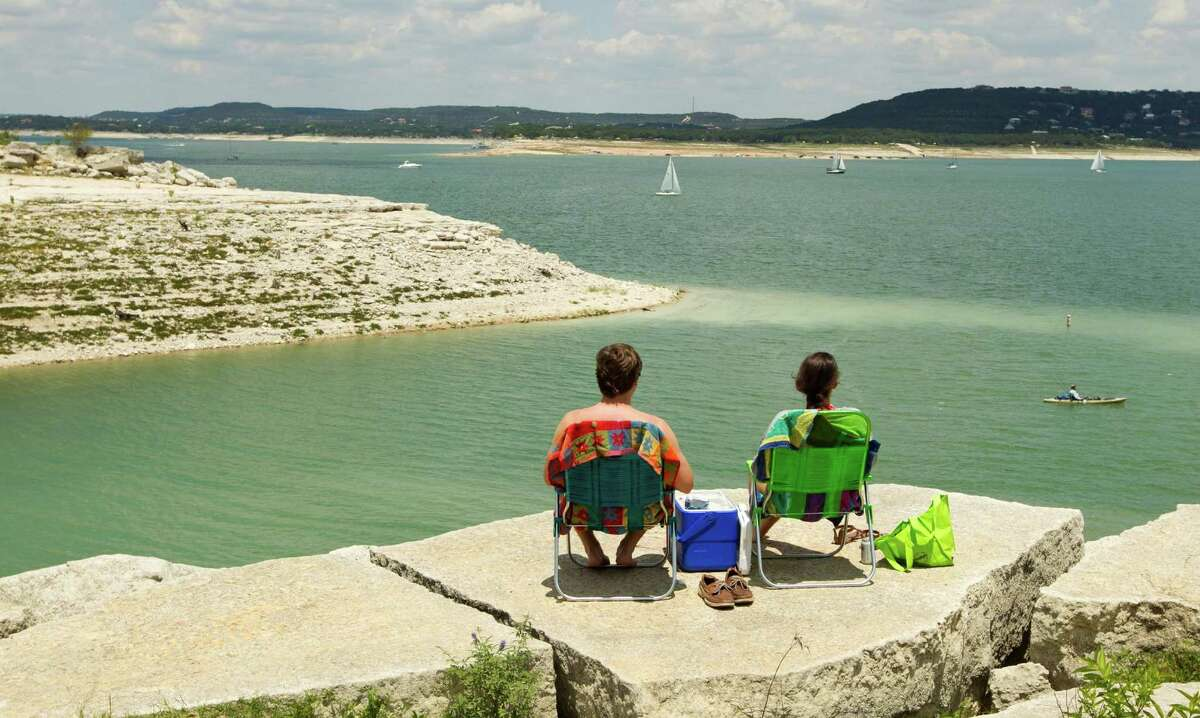 Taylor Denson and his girlfriend, Ali Mills, enjoy the view of Lake Travis from the Mansfield Dam Recreation Park. A stifling drought has exacerbated water needs along the lakes as reacreation and agriculture vie for an equitable share.