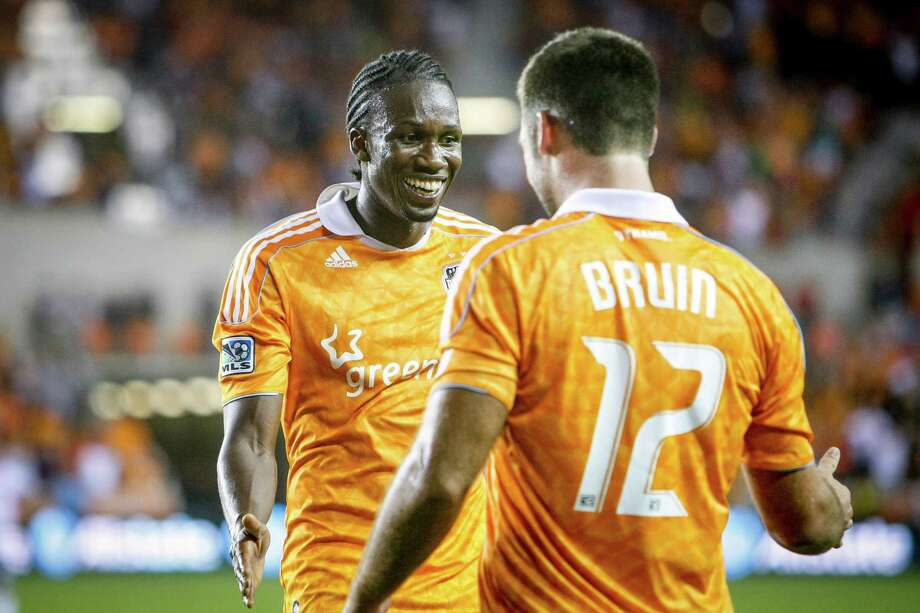 Dynamo midfielder Macoumba Kandji (9) celebrates with forward Will Bruin (12) after he scored a goal. Photo: Michael Paulsen, Houston Chronicle / © 2012 Houston Chronicle