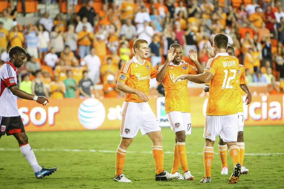 Dynamo midfielder Luiz Camargo (17) celebrates with forward Will Bruin (12) after assisting him on a goal. Photo: Michael Paulsen, Houston Chronicle / © 2012 Houston Chronicle
