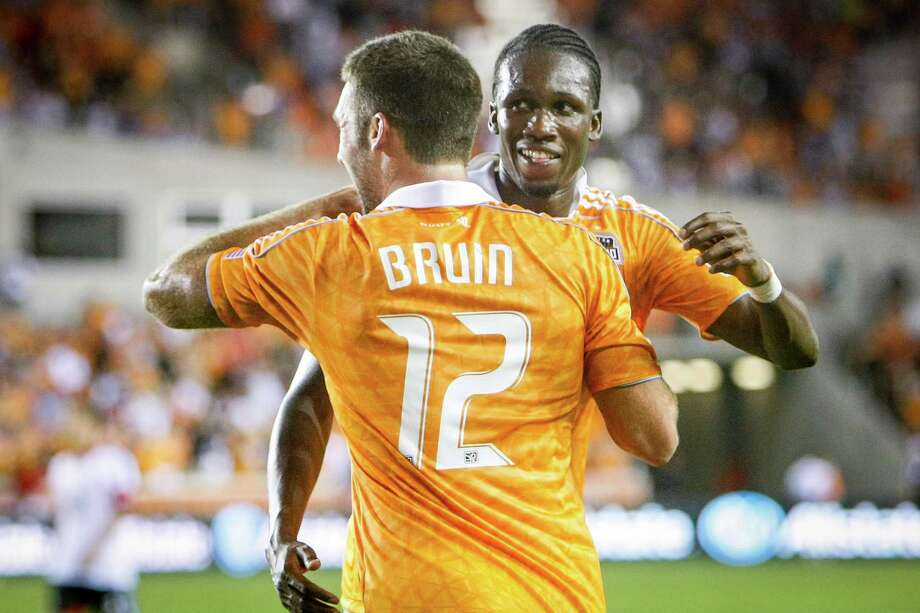 Dynamo midfielder Macoumba Kandji celebrates a goal with teammate Will Bruin (12). Photo: Michael Paulsen, Houston Chronicle / © 2012 Houston Chronicle