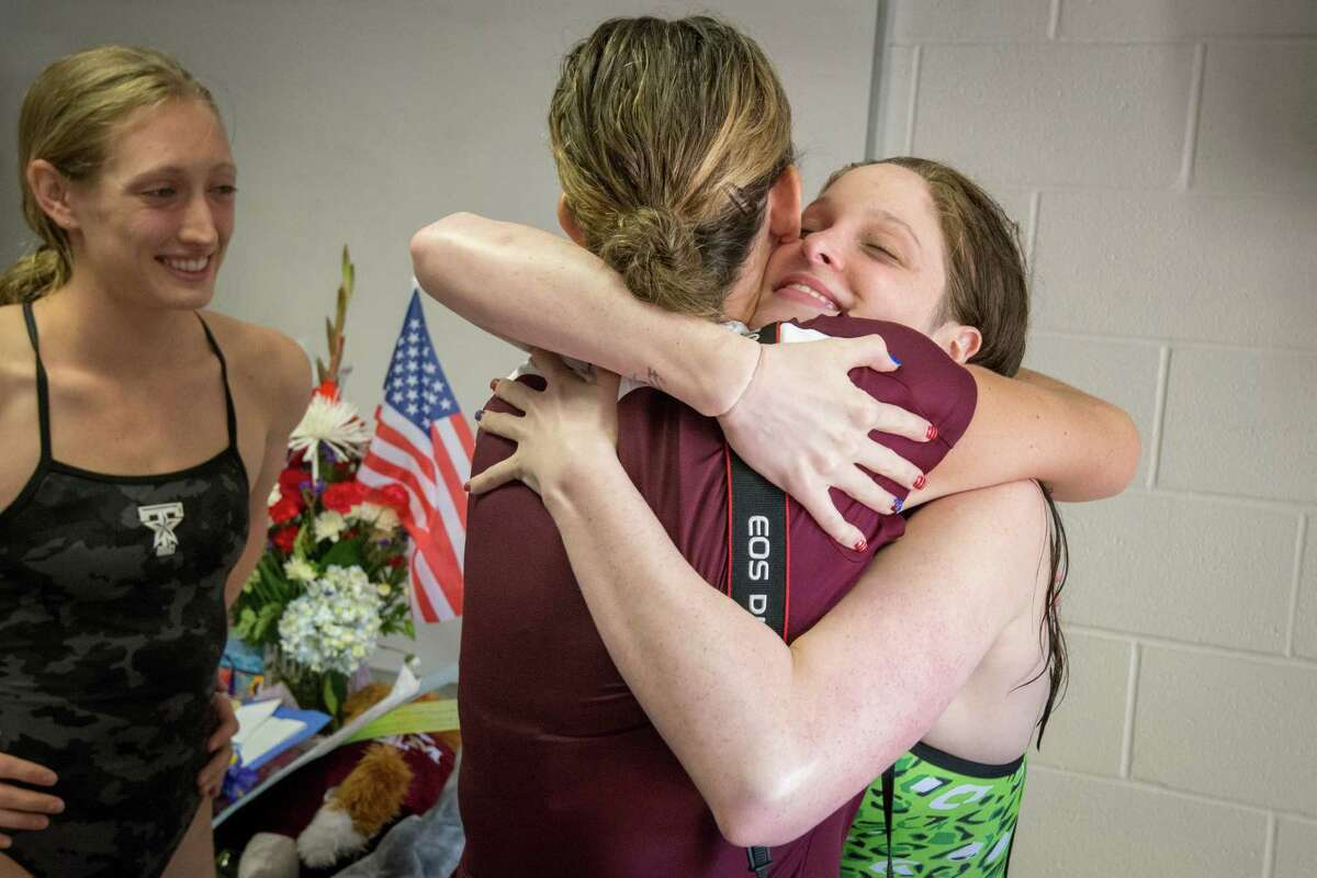 At a recent party to honor Texas A&M's representatives on the U.S. swim team, Cammile Adams, right, gets a hug from a well-wisher alongside fellow Aggie and Olympian Breeja Larson, left.