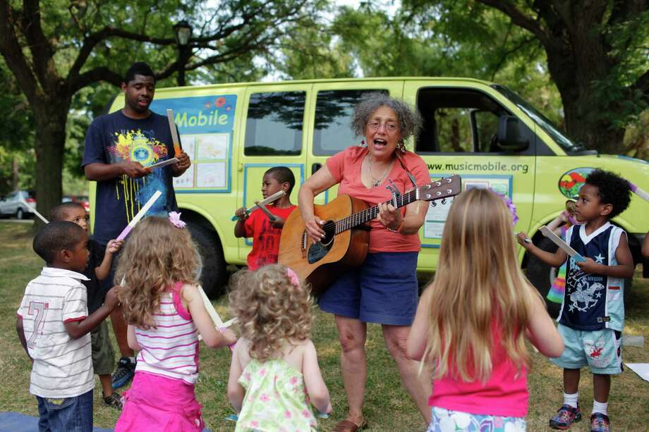 "Ruth Pelham, founder of the Music Mobile, leads children in song while they play their ""peace wand"" instruments in Washington Park, Friday afternoon July 13, 2012, in Albany, N.Y. (Dan Little / Special to the Times Union) Photo: Dan Little / Copyright: All Rights Reserved Brett Carlsen"