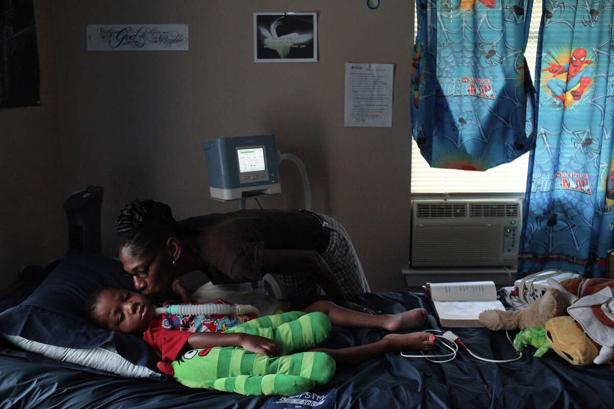 Rhodena Matthews, kisses her grandson, Braylon Nelson, 2, who was paralyzed in a road rage accident, at his home in San Antonio on Friday, June 29, 2012.