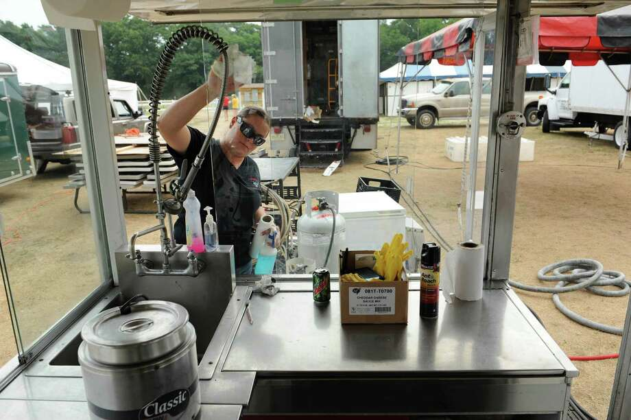 Diana Rowlett from Edmond, Oklahoma cleans the glass on the Valentino's London Broil food stand at the  Saratoga County Fair grounds on Sunday, July 15, 2012 in Ballston Spa, NY.  Rowlett works for Vinny Valentino who owns and also operates the stand.  This is their fourth year at the fair.  The fair opens on Tuesday.   (Paul Buckowski / Times Union) Photo: Paul Buckowski