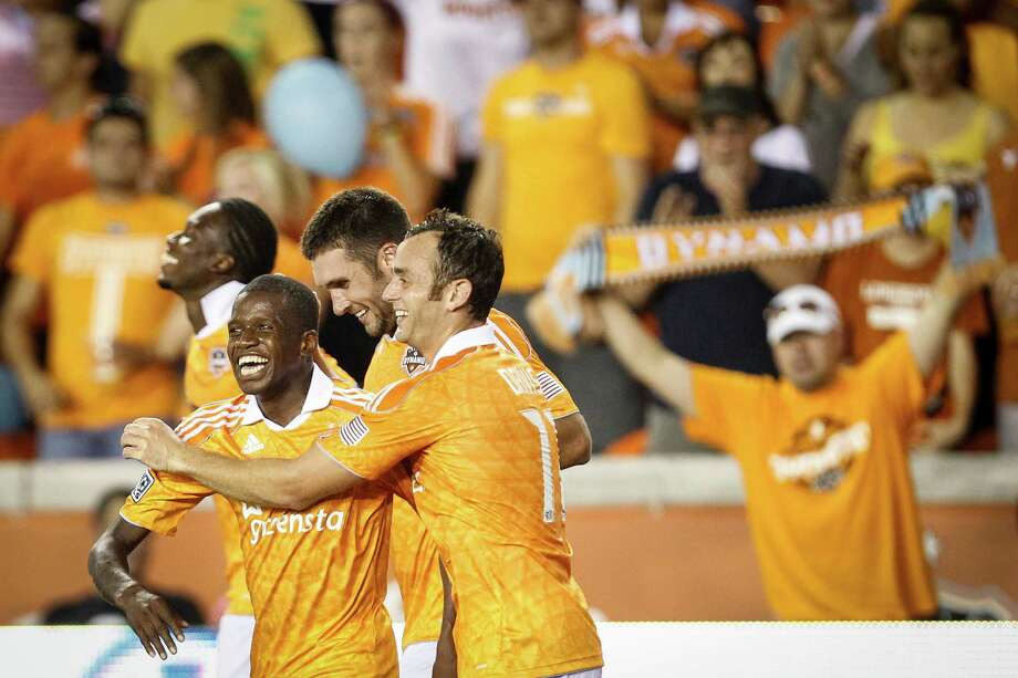 Dynamo midfielder Brad Davis (11) hugs forward Boniek Garcia (27) after Garcia scored a goal. Photo: Michael Paulsen, Houston Chronicle / © 2012 Houston Chronicle