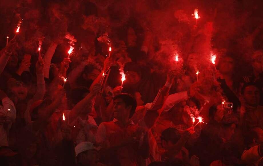 Independiente Santa Fe fans celebrate after their team won the Liga Postobon local soccer league tournament match against Deportivo Pasto in Bogota, Colombia, Sunday, July 15, 2012. Santa Fe won 1-0. Photo: William Fernando Martinez, Associated Press
