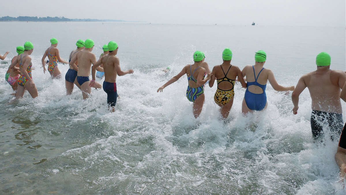Swimmers take the plunge Sunday for the annual Point to Point Swim, sponsored by the Westport Weston Family Y, at Compo Beach.
