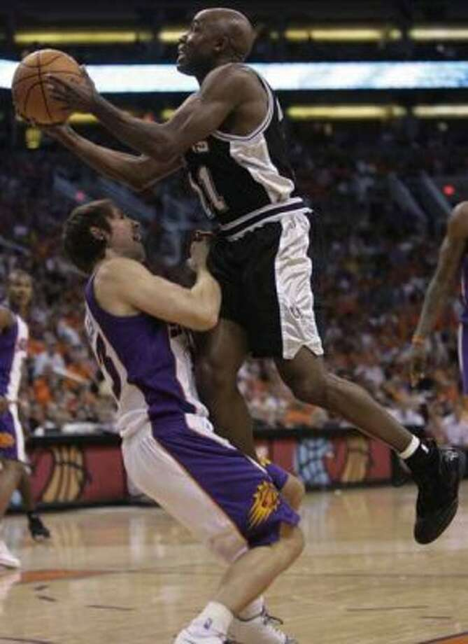 Spurs guard Jacque Vaughn drives to the hoop and through the Phoenix Suns' Steve Nash during Game 1 of the second round of the Western Conference playoffs in Phoenix on May 6, 2007. Vaughn was called for a foul on the drive. (William Luther / San Antonio Express-News)