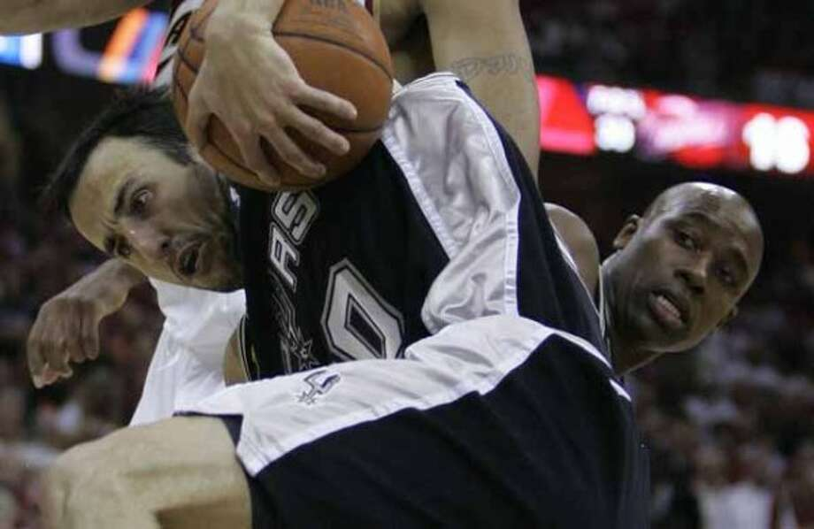 Spurs guard Manu Ginobili controls a loose ball as guard Jacque Vaughn looks on during Game 3 of the NBA Finals in Cleveland on June 12, 2007. (Tony Dejak / Associated Press)