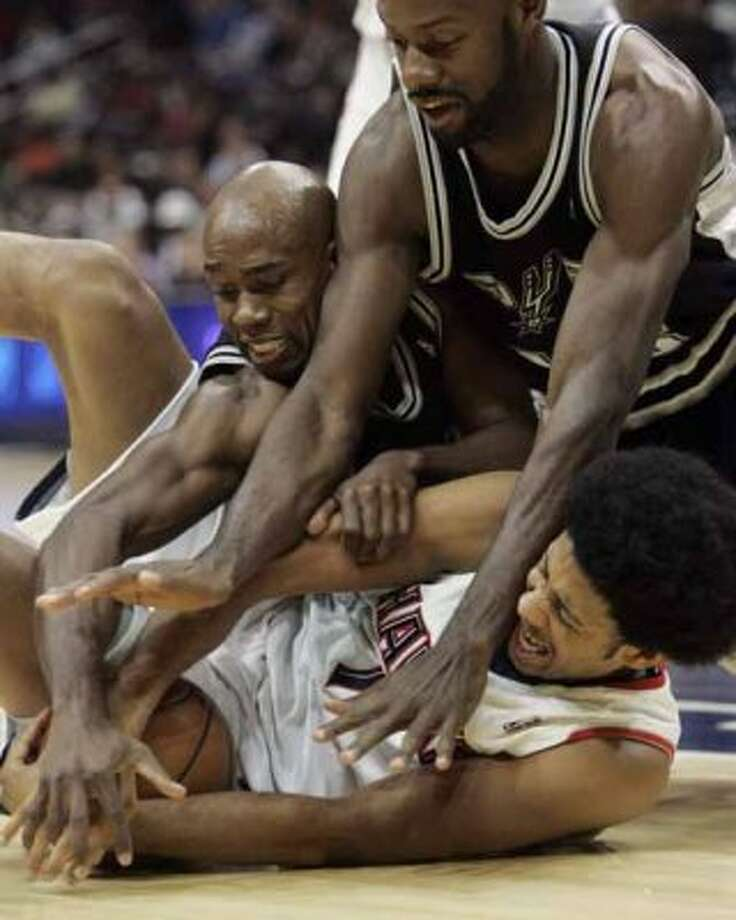 Spurs guard Jacque Vaughn (left) center Francisco Elson fight the Atlanta Hawks' Josh Childress for the ball on Nov. 20, 2007 in Atlanta. (John Amis / Associated Press)